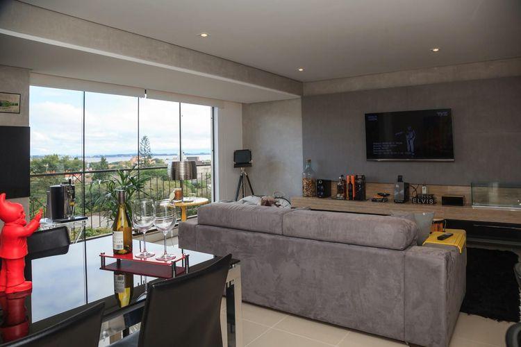 Sala de estar com janela grande de Vidro de Braccini + Lima